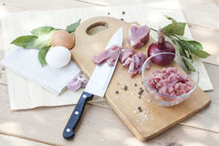 Raw chopped pork tenderloin with herbs in a glass bowl on a wooden board Royalty Free Stock Photo