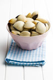 Raw clams in ceramic bowl. On white wooden table Royalty Free Stock Photos