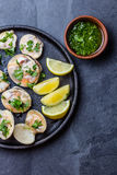 Raw clams with lemon, herbs and white wine, slate background. Fresh raw clams with lemon, herbs and white wine on blackiron plate on stone slate background. Top Stock Photo