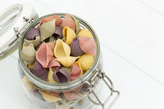 Raw cocciolette pasta on a glass jar. On blue wood table Stock Photography