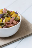 Raw cocciolette pasta in a white bowl. On blue wood table Royalty Free Stock Photography