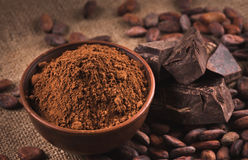 Raw cocoa beans, clay bowl with cocoa powder, chocolate on sack. Cocoa beans, clay bowl with cocoa powder, black chocolate on brown sacking