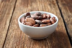 Raw cocoa beans in a white bowl. On a wooden table stock image