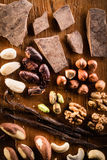 Raw cocoa mass with hazelnuts. Walnuts, cashews and vanilla orchid pod on the grunge table or desk in the kitchen. Composition of the ingredients for cooking royalty free stock photos