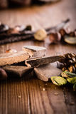 Raw cocoa mass with hazelnuts,. Walnuts, cashews and vanilla orchid pod on the grunge table or desk in the kitchen. Composition of the ingredients for cooking royalty free stock image