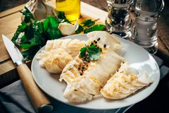 Raw cod fillet on white plate. Garlic, oil and parsley in the background Stock Image