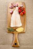 Raw cod fillet on wooden board. Raw cod fillet with garlic, tomato, thyme and lemon on wooden board Royalty Free Stock Images