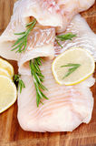 Raw Cod Fish. Fillet with Lemon Slices and Rosemary closeup on Wooden background. Vertical View Royalty Free Stock Photos