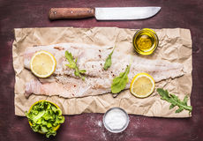 Raw cod with lemon and herbs, salt and butter and a knife on paper on wooden rustic background top view close up Stock Images
