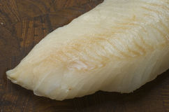 Raw Cod on a wooden butcher. Close up of fresh raw cod fillet on a wood cutting board Royalty Free Stock Photo