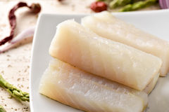 Raw codfish. Closeup of some slices of raw codfish in a white ceramic plate, on a rustic wooden table stock photography