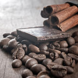 Raw coffee beans and chocolate. On old wooden plank Royalty Free Stock Images