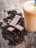 Raw coffee beans and chocolate. On old wooden plank Stock Photos