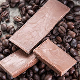 Raw coffee beans and chocolate. On old wooden plank Stock Image