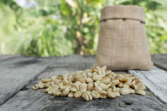 Raw coffee beans on green blurred background.  Royalty Free Stock Photos