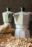 Raw coffee beans with moka pot in a sack on table Royalty Free Stock Image