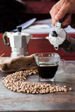 Raw coffee beans with moka pot in a sack on table Royalty Free Stock Photography