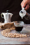 Raw coffee beans with moka pot in a sack on table Stock Photos