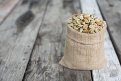 Raw coffee beans on Wood background.  Royalty Free Stock Images