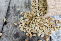 Raw coffee beans on Wood background.  Royalty Free Stock Photos
