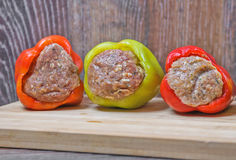 Raw Colored bell peppers stuffed with meat on a cutting Board Royalty Free Stock Images