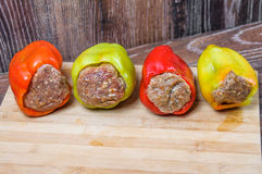 Raw Colored bell peppers stuffed with meat on a cutting Board Royalty Free Stock Photo
