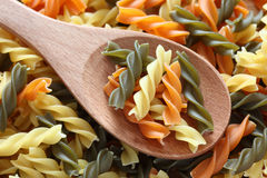 Raw colorful fusilli pasta on a wooden spoon. On a fusilli pasta background. Close-up Stock Images