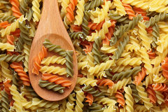 Raw colorful fusilli pasta in a wooden spoon Stock Photography