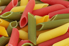 Raw colorful penne. Close-up of lots of raw colorful pasta Stock Images