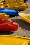Raw of colourful canoes on beach. Bright colourful canoes lie on sand in one row in sunny weather Stock Images