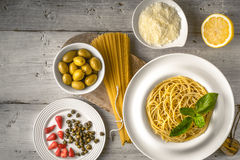 Raw and cooked spaghetti with different appetizer on the white wooden table top view. Concept of Italian cuisine Royalty Free Stock Photos