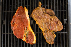 Raw an Cooked. Two pieces of steak on the grill Stock Images