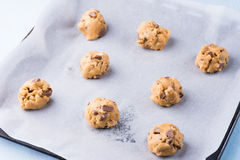 Raw cookie dough on a baking tray with parchment paper. Selective focus royalty free stock photo