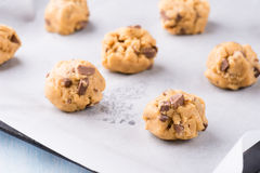 Raw cookie dough on a baking tray with parchment paper. Selective focus stock photos
