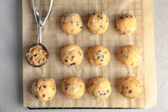 Raw cookie dough with chocolate chips and scoop. On parchment paper, top view Royalty Free Stock Photos