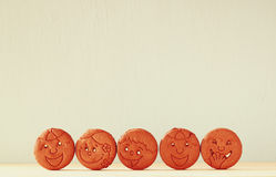Raw of cookies with smiley face over wooden table Stock Photos