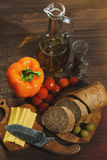 Raw cooking ingredients on the wooden table. Cooking ingredients suitable for mediterranean cuisine: bell pepper, cherry tomatoes, fresh baguette bread, cheese stock photography