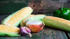 Raw corn on the cob on a green wooden background, vegetables. Raw corn on the cob Stock Images