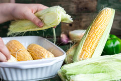 Raw corn on the cob, prepare them for baking, hands. On a green wooden background Stock Photography