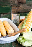 Raw corn on the cob to cook bake,green background. Raw corn on the cob to cook bake on a green wooden background Stock Photo