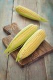 Raw corn cobs. On wooden background closeup Stock Photos
