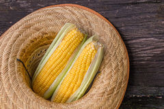 Raw corn. With hat on the wooden floor Stock Photo