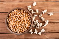 Raw corn seeds in wooden bowl and popped popcorn on table. Raw corn seeds in wooden bowl and popped popcorn on retro wooden table, top view Royalty Free Stock Images