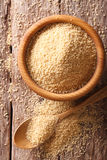 Raw Couscous in a wooden bowl and spoon close-up. vertical top v Royalty Free Stock Images