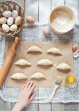 Raw croissants on parchment, preparation process. Royalty Free Stock Photography