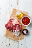 Raw cross cut veal shank and Ingredients for Osso Buco. Raw fresh cross cut veal shank and Ingredients for making Osso Buco on blue background Stock Image