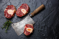 Raw cross cut veal shank for making Osso Buco. Raw fresh cross cut veal shank for making Osso Buco on black background with meat cleaver Stock Photo