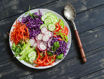 Raw crunchy colorful Coleslaw with red cabbage, radish, cucumber, sweet peppers, carrots, parsley and sesame seeds. Stock Photos