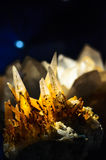 Raw crystals with gold in darkness Royalty Free Stock Photo