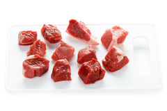 Raw cubes lamb on a chopping board Royalty Free Stock Images